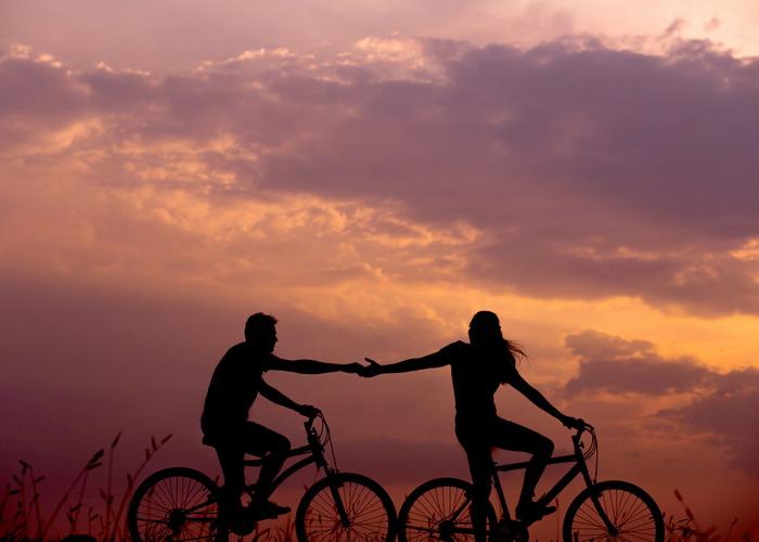 Egy férfi és egy nő kerékpáron fogja egymás kezét a naplementében