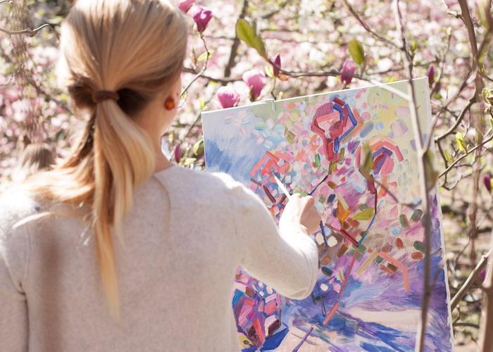 Egy szőke nő virágzó bokrot fest napsütésben