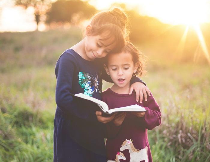 Két kislány könyvet olvas